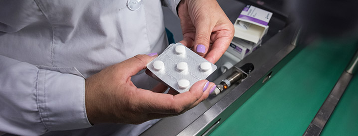 A lady's hands holding pill packaging