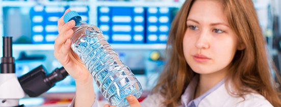 Woman examining a bottle for food and beverage quality control